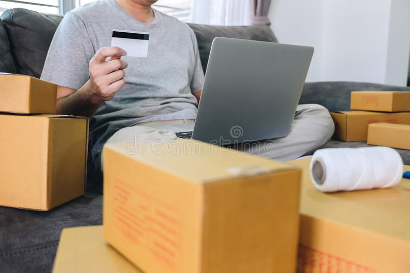 Small business parcel for shipment to client, Young man received online shopping parcel opening boxes and buying items by credit. Card, online marketing on royalty free stock image