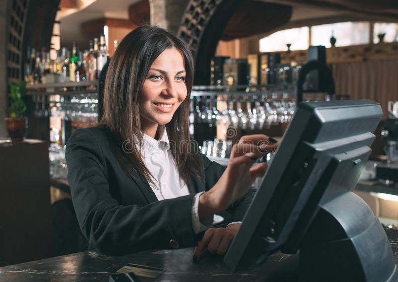 Small business, people and service concept - happy woman or waiter or manager in apron at counter with cashbox working stock photos