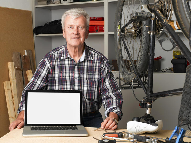 Small business. Portrait of senior bike shop owner sitting at desk behind the laptop with white screen. Active old man looking at camera and smiling. Small royalty free stock images