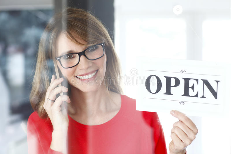 Small business. Portrait of a smiling middle aged woman making call while holding up a sign on opening day of her small business royalty free stock image