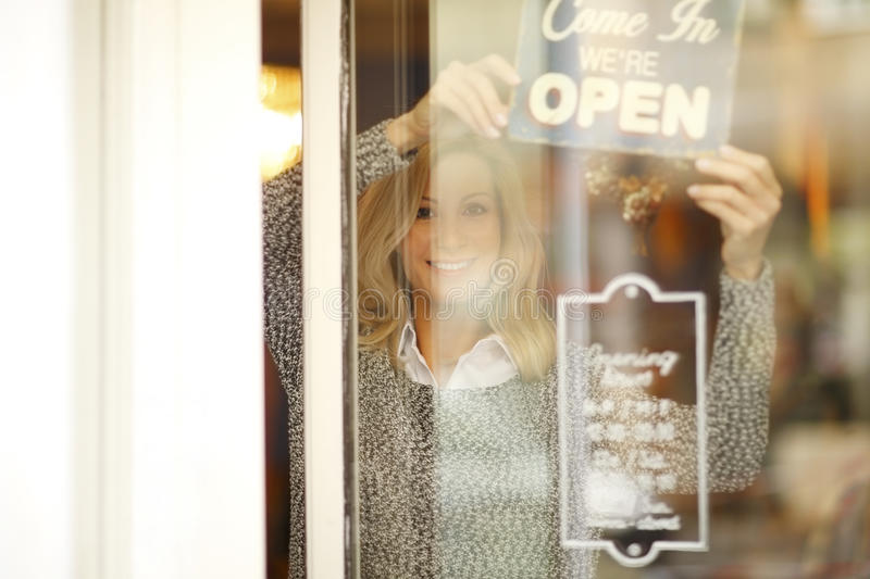 Small business. Portrait of smiling woman standing behid her clothing store shop window. Small business stock photo