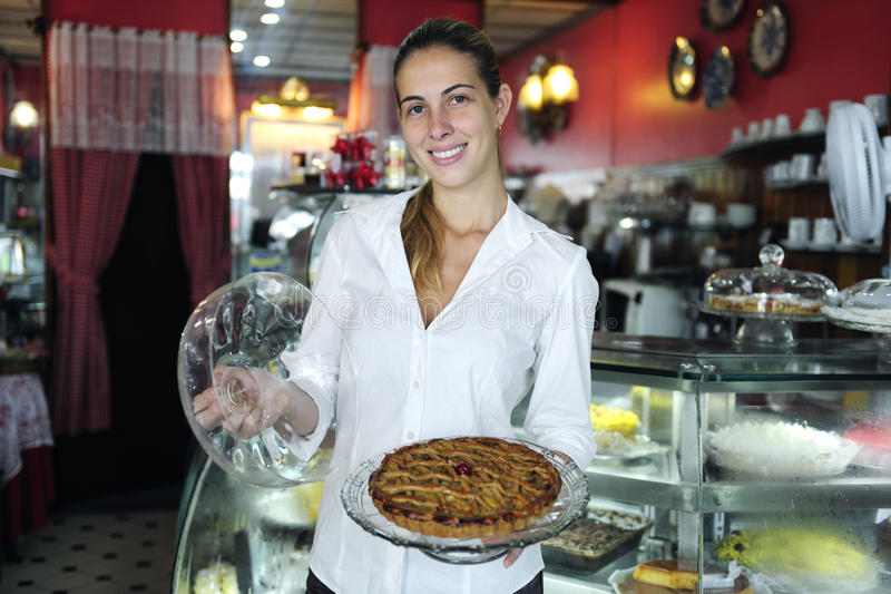 Small business: proud female owner of a cafe. Showing a cake royalty free stock photo