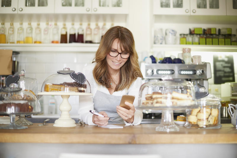 Small business. Shot of a confident woman using mobile phone and doing some paperwork while standing behind the counter in her small cafe. Small business stock photography