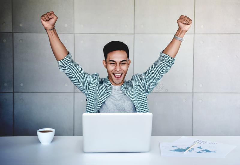 Small Business and Successful Concept. Young Asian Businessman Glad to recieve a Good News or High Profits from Computer Laptop, royalty free stock photos