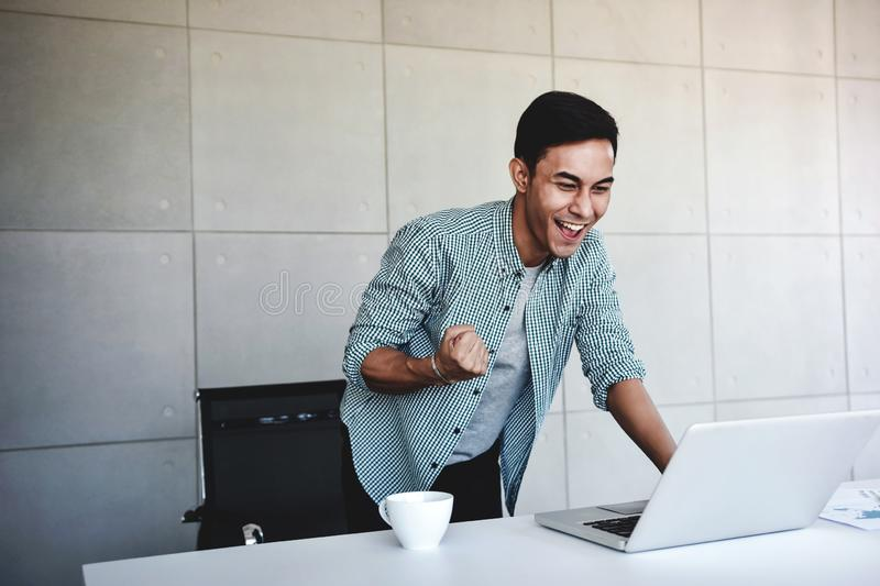 Small Business and Successful Concept. Young Asian Businessman Glad to recieve a Good News or High Profits from Computer Laptop, stock images