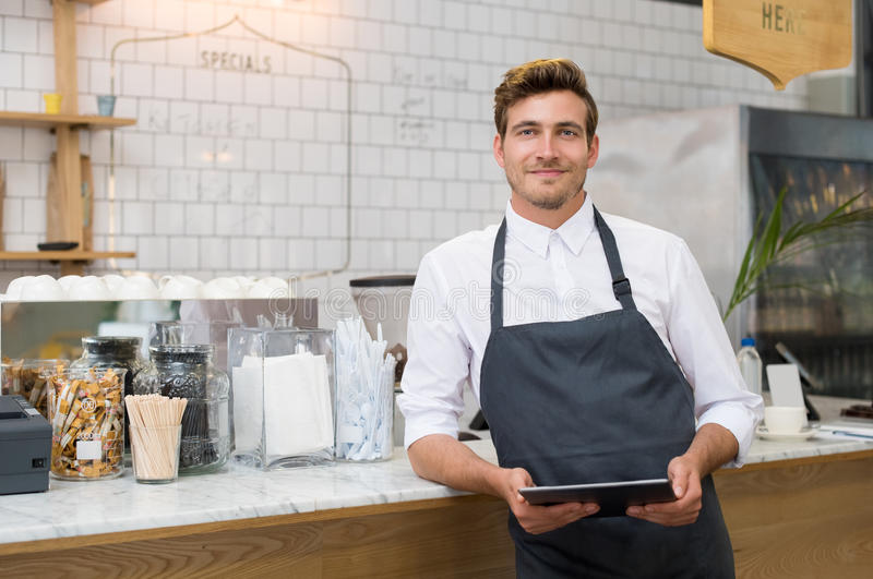Small business. Successful small business owner holding digital tablet and looking at camera. Happy smiling waiter with apron and digital tablet leaning on royalty free stock photography