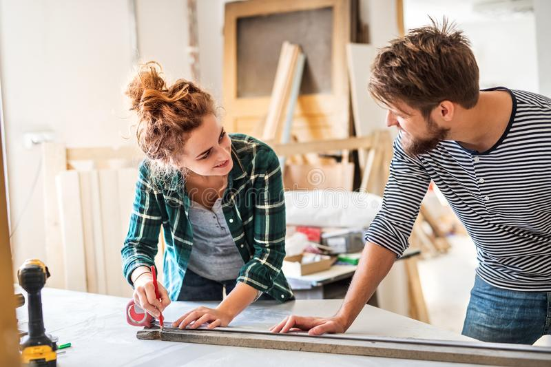 Small business of a young couple. Man and women worker in the carpenter workroom royalty free stock photos