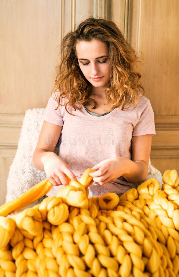 Small business of a young woman. Young woman hand-knitting a wollen blanket stock image