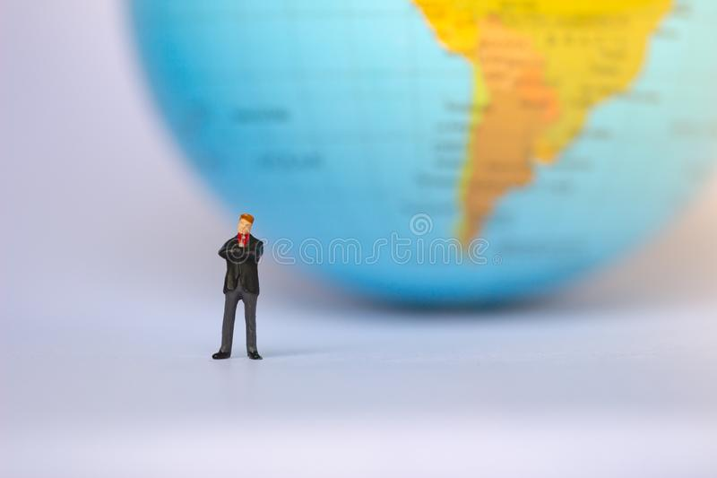 Small businessman figures standing on turning point on earth background. stock photos