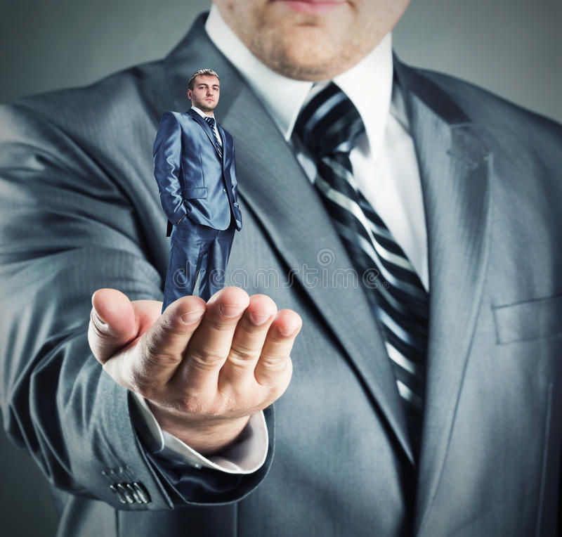 Small businessman in hand royalty free stock image