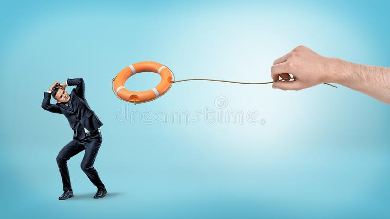 A small businessman hiding from an orange life buoy thrown down by a giant male hand. royalty free stock photo