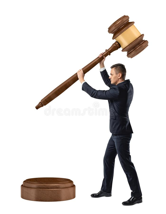 A small businessman on isolated white background holds and lowers a giant judge gavel on a sound block. stock photos