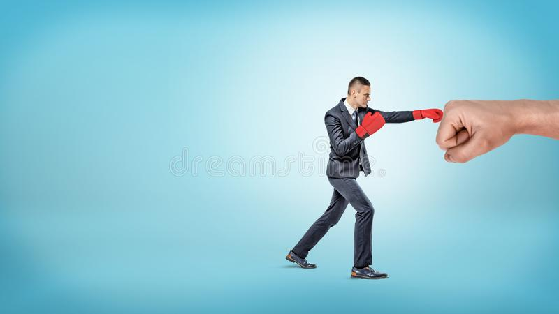 A small businessman in red boxing gloves punches a giant male fist on blue background. stock photography