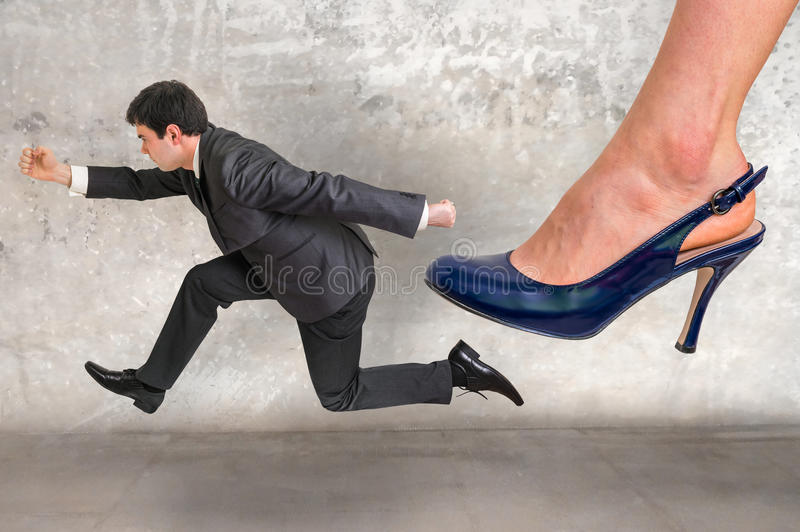 Small businessman running away from a boss pressure stock image