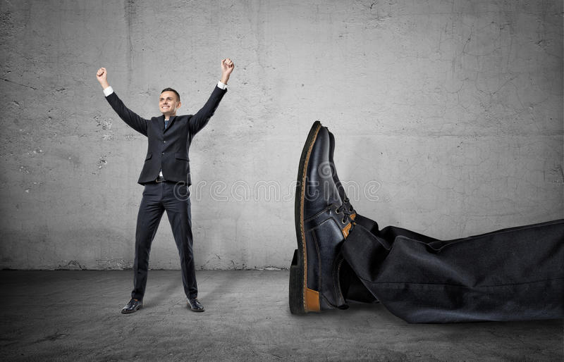 Small businessman standing with his arms up near giant leg of another man stock image