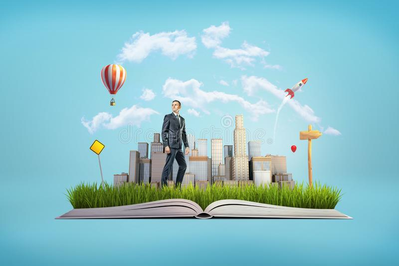 A small businessman standing on pages of an open book which is a basis for a small city. Dream business. Business vision. Personal coaching royalty free stock photos