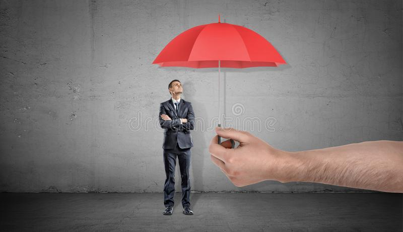 A small businessman stands looking up on a red open umbrella offered by a giant male hand. Unexpected assistance. Business support. Corporate insurance royalty free stock image