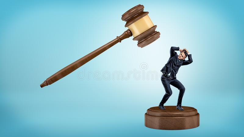A small businessman tries to avoid a giant gavel strike while standing on a sound block. royalty free stock photo