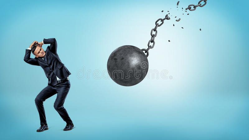 A small businessman trying to hide and cover himself from a falling wrecking ball with a torn chain. royalty free stock photos