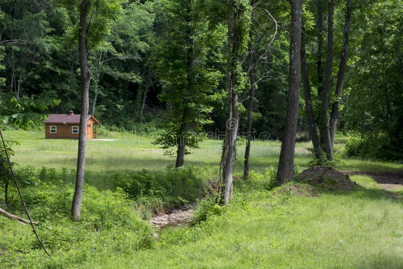 Meadow with small cabin and stream stock photos