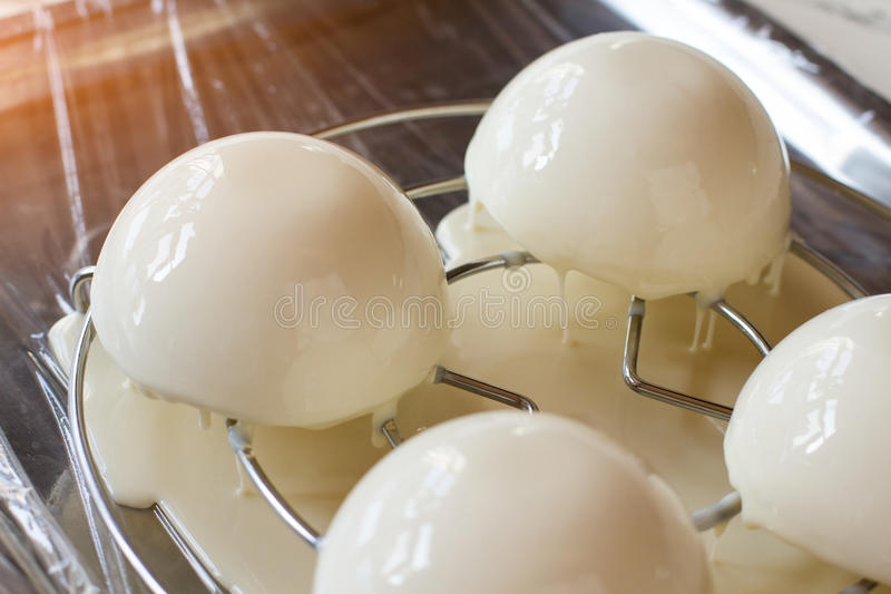 Small cakes with liquid glaze. White sweets on small rack. Desserts with taste of vanilla. Mousse and mirror icing stock photos