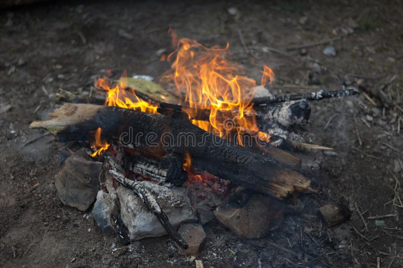 A small campfire made up of twigs and branches with rocks surrounding it. Ready for a night of camping under the stars stock images