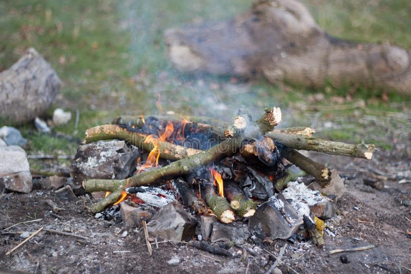 A small campfire made up of twigs and branches with rocks surrounding it. Ready for a night of camping under the stars stock photography
