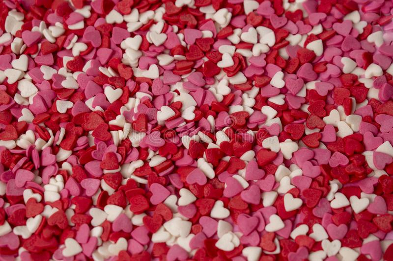 Small candy in the shape of a heart is scattered over the background. Many bright hearts in bulk. Pink, red, white candy royalty free stock image
