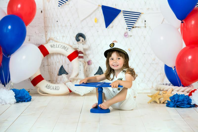 The small captain sits on the floor in a marine style. We mark the first year. stock photo