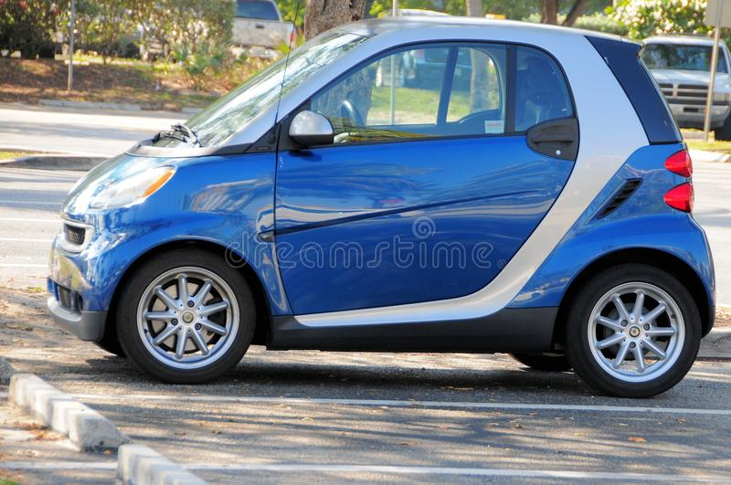 Small car in parking lot, South Florida. Blue and white Smart car in a parking lot in South Florida stock photos
