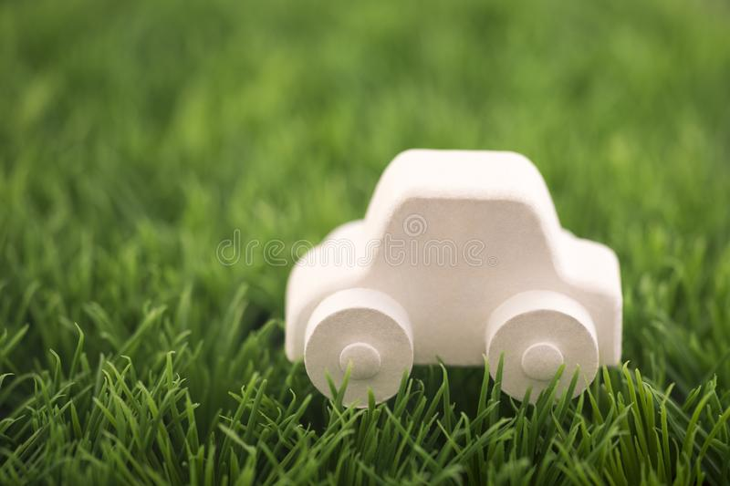 Car toy on green grass. Eco driving concept royalty free stock image