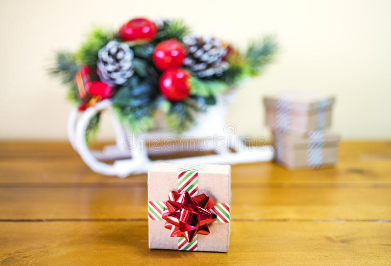 Small cardboard giftbox wrapped in striped ribbon and shiny holiday bow, decorative Christmas sleigh stock photos