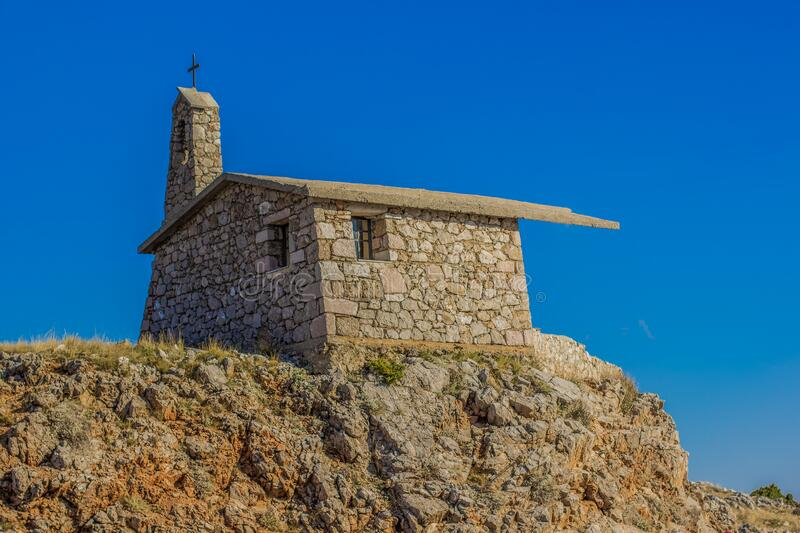 Small catholic church on top mountain rock nature landscape pilgrim place on blue empty sky background royalty free stock image