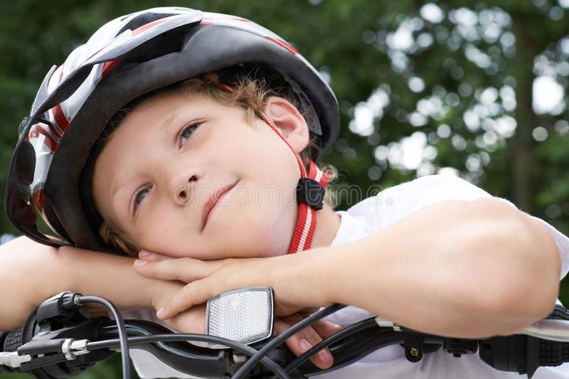 Small Caucasian boy cyclist in protective helmet put his head on the handlebar of the bike posing for the camera. a Boy stock photography