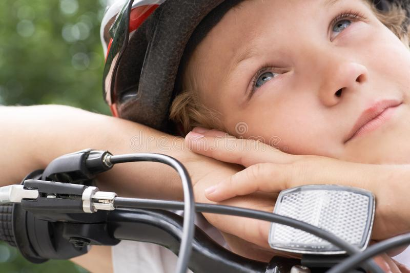 Small Caucasian boy cyclist in protective helmet put his head on the handlebar of the bike posing for the camera. a Boy stock photo