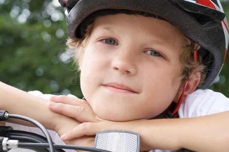 Small Caucasian boy cyclist in protective helmet put his head on the handlebar of the bike posing for the camera. a Boy royalty free stock image