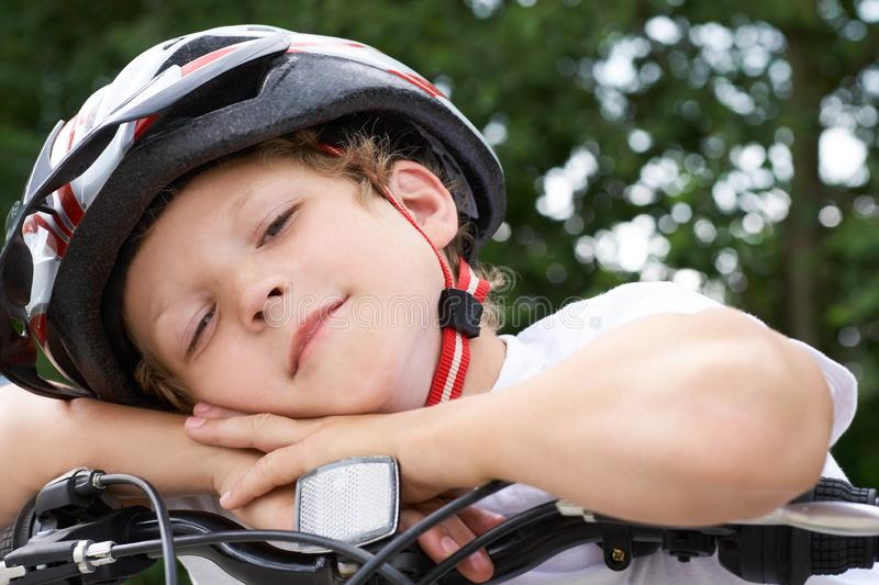 Small Caucasian boy cyclist in protective helmet put his head on the handlebar of the bike posing for the camera. a Boy royalty free stock photo