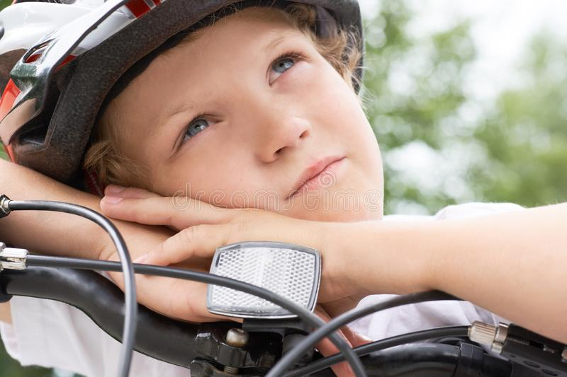Small Caucasian boy cyclist in protective helmet put his head on the handlebar of the bike posing for the camera. Boy stock photography