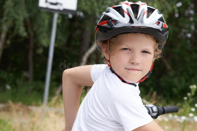Small Caucasian boy in protective helmet stands leaning on the bike posing for the camera. Teenager ready to ride. Bicycle in park on summer day royalty free stock photos