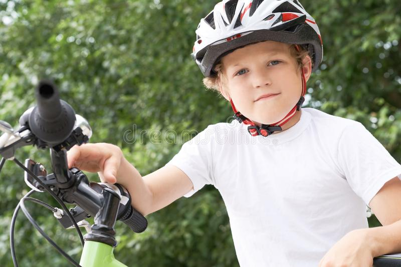 Small Caucasian boy in protective helmet stands leaning on the bike posing for the camera. Teenager ready to ride. Bicycle in park on summer day royalty free stock image