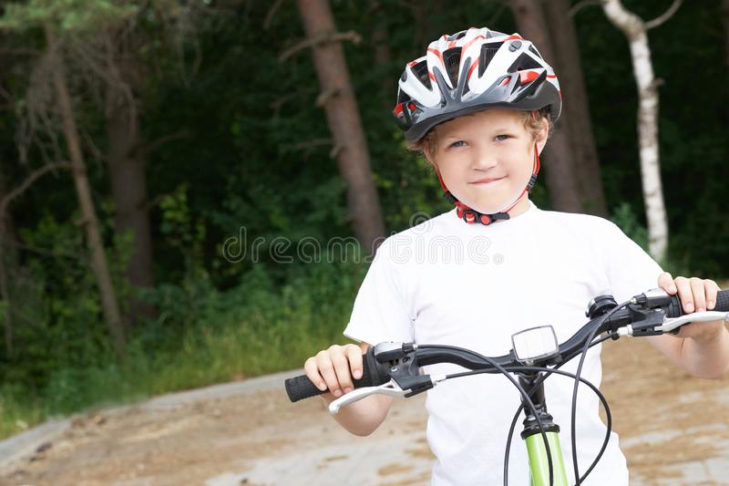 Small Caucasian boy in protective helmet stands leaning on the bike posing for the camera. Teenager ready to ride. Bicycle in park on summer day royalty free stock photography