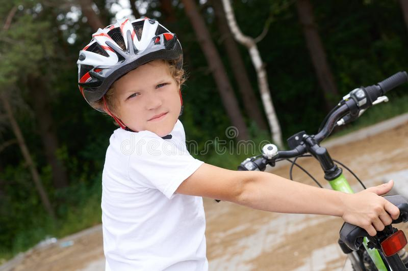 Small Caucasian boy in protective helmet stands leaning on the bike posing for the camera. Teenager ready to ride royalty free stock photography