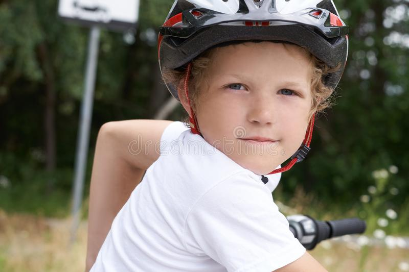 Small Caucasian boy in protective helmet stands leaning on the bike posing for the camera. Teenager ready to ride stock photography
