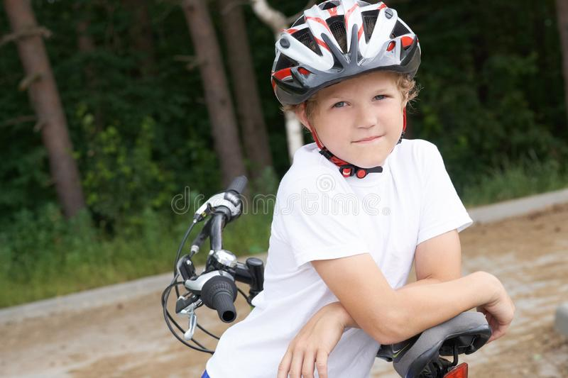 Small Caucasian boy in protective helmet stands leaning on the bike posing for the camera. Teenager ready to ride royalty free stock image