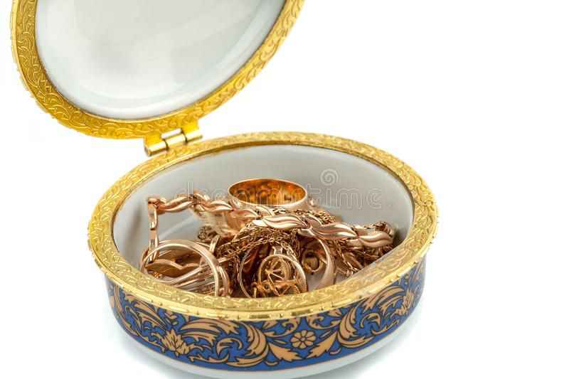 Small ceramic box with gold jewelry in it on white background royalty free stock photo