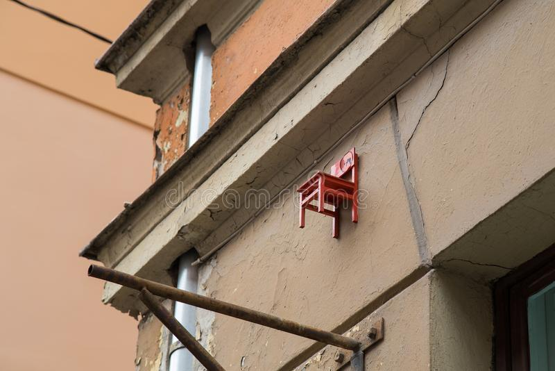 Small red chair on the building in Riga, Latvia. Small chair on top of the building in Riga, Latvia. Building is located in old town in Riga stock images