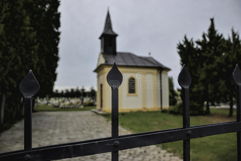 A small chapel at the cemetery in Jacovce near Topolcany, Slovakia, Europe. Gate to the small church. Roman Catholic Church stock photo