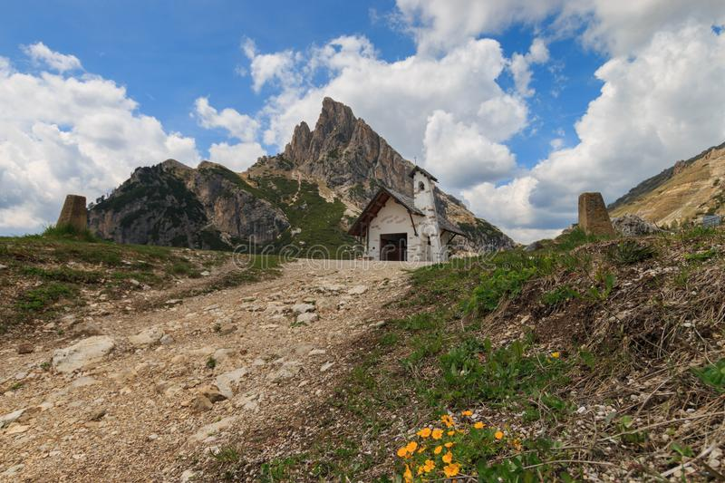 Small chapel at Falzarego Pass, Italy. Small white chapel with Sass de Stria mountain on top of Falzarego pass in the Dolomites, Italy royalty free stock images