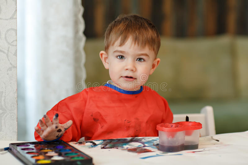 Small charming baby boy in a red robe draws colored paint sitting at the table at home stock photos