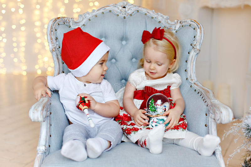 Small charming baby boy in red Santa hats and the little blond g stock image